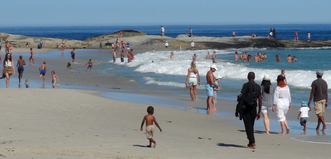 People strolling on Camps Bay beach next to the surf