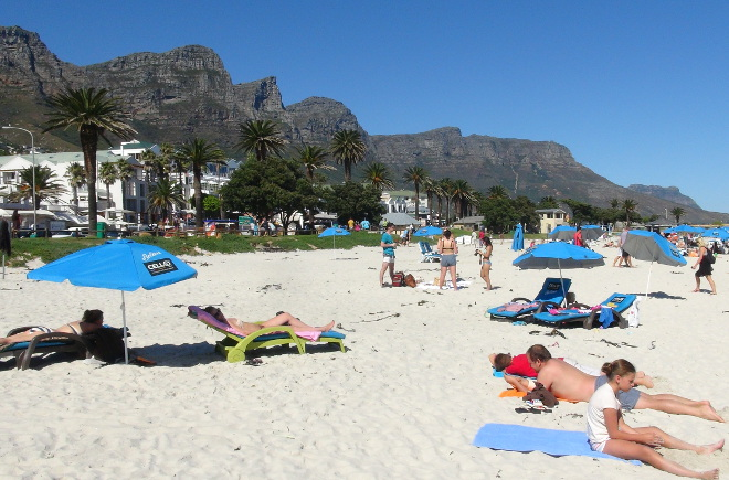Camps Bay beach in Cape Town, with sunbathers & the 12 Apostles Mountain Range in the background.