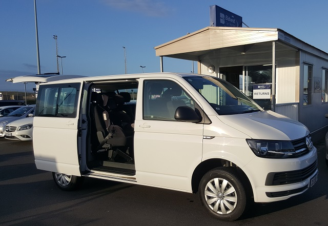 VW Kombi with boot and sliding door open, next to a Bidvest Car Rental kiosk; at King Shaka International Airport