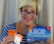 A happy Mango Airlines passenger poses with plane tickets and their in-flight magazine